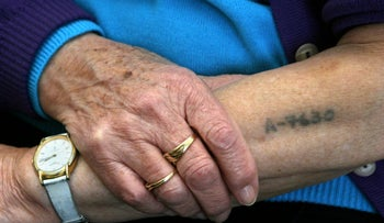 File photo: Holocaust survivor Bracha Ghilai, 75, shows her tattooed arm at her house in Holon , Israel, January 23, 2005.