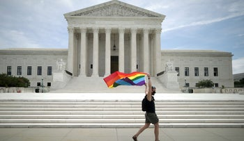 An activist holding a Pride Flag running in front of the U.S. Supreme Court building in Washington after the court ruled that LGBTQ people can not be disciplined or fired based on their sexual orientation, June 15, 2020.