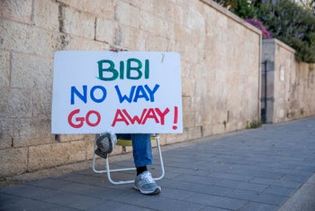 A protester holds a sign at a demonstration again Prime Minister Benjamin Netanyahu, June 23, 2020