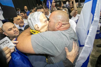 A supporter of Prime Minister Benjamin Netanyahu kisses a Netanyahu mask on election night, March 2020