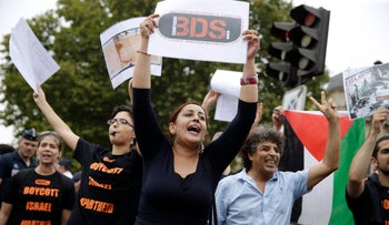 """A pro-Palestinian protester holds a placard reading """"BDS"""" during a gathering on the sidelines of an event celebrating Tel Aviv, in central Paris, August 13, 2015"""