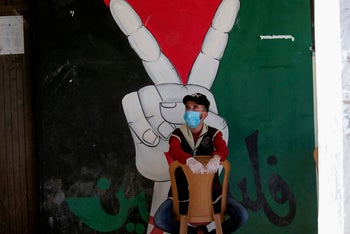"""A Palestinian man sits on a chair in front of a mural reading """"Palestine"""" depicting a hand flashing the victory sign, at a rally against annexation in the Jordan Valley village of Bardal. June 27, 2020"""