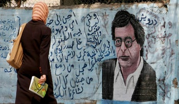 A woman walks past a mural of the late Palestinian poet Mahmud Darwish in Jenin, West Bank, September 2, 2008.