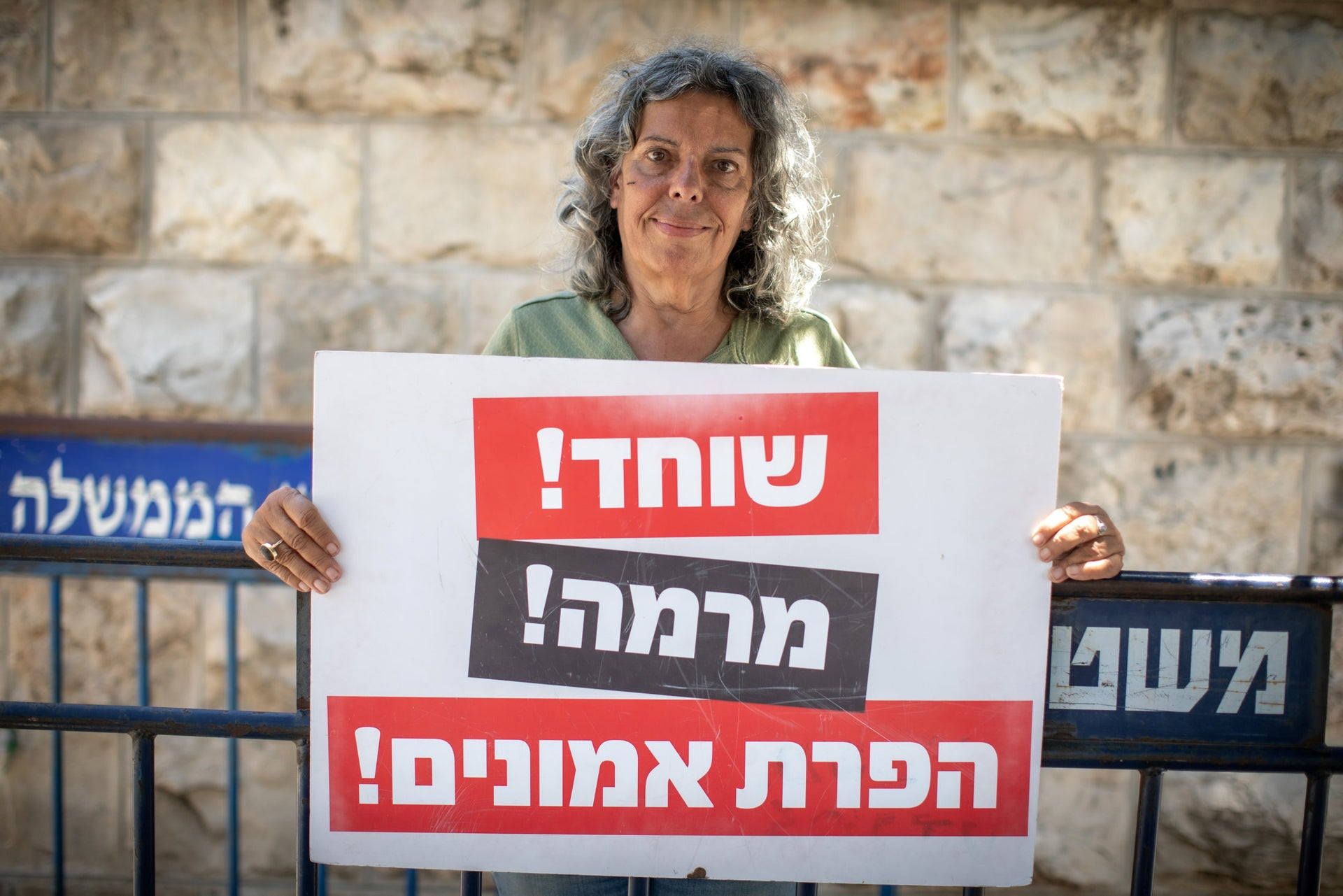 Yafa Yousef holding a sign reading: 'Bribe, fraud, breach of trust,' while demonstrating in Jerusalem, June 16, 2020.