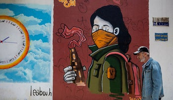 A man walks past a mural depicting an anti-government protester wearing a mask and holding a molotov cocktail in Beirut, Lebanon, May 2, 2020.