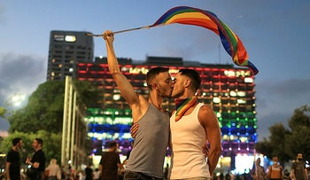 A couple celebrate Pride in front of the LGBTQ flag lit Tel Aviv Municipality, June 28, 2020.