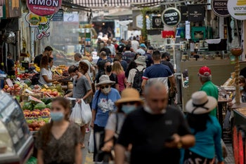 People shop in the Mahane Yehuda market in Jerusalem, Israel, June 17, 2020.