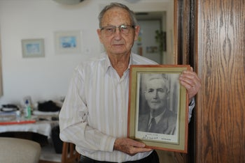 Shmuel Elbaz of Haifa with a picture of his father, Shimon Elbaz, whose life was saved in 1929 by an Arab friend named Karim al-Shatti.