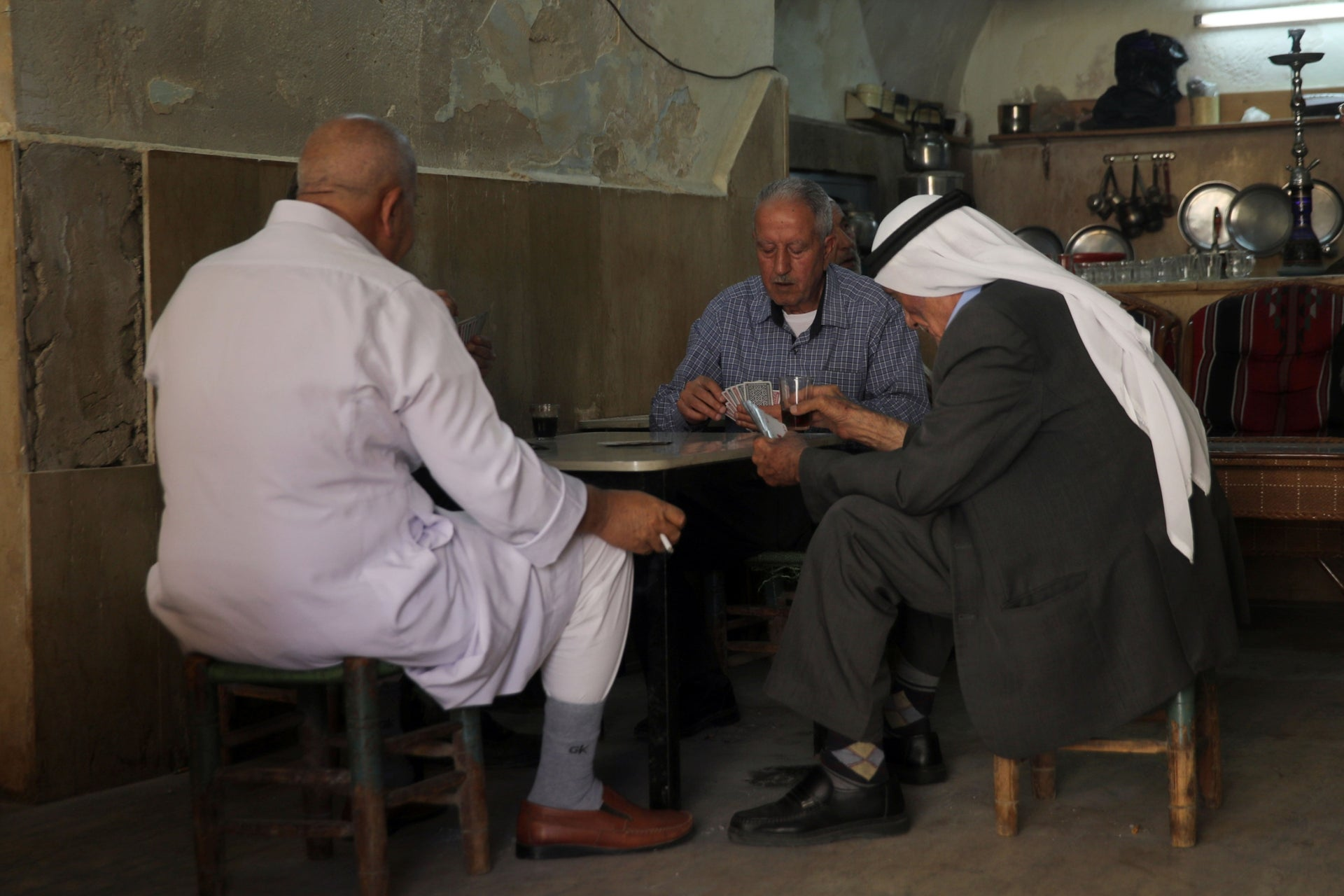 A group of men playing cards in a West Bank cafe.