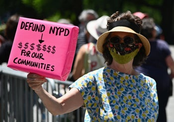 An elderly protester holds a sign during a rally outside City Hall across from One Police Plaza to demand less funding for the New York Police Department (NYPD), New York City, June 24, 2020.