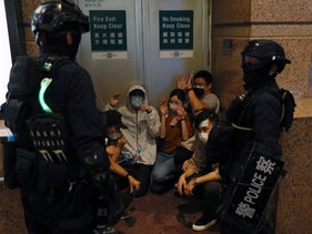 People detained by riot police during a march against national security law at the anniversary of Hong Kong's handover to China from Britain in Hong Kong, July 1, 2020.