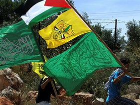 Palestinian protesters carry the Hamas (bottom) and Fatah (C) flags during a rally on May 6, 2011, in the Israeli-occupied West Bank village of Bilin.