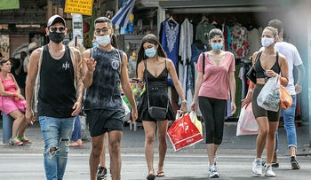 People wearing protective masks against COVID-19 walk in the streets of Tel Aviv, June 29, 2020.