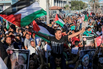 Protesters waves national flags and hold posters of Mahmud Abbas during a demonstration against Israel's annexation plans, in Khan Yunis in the southern Gaza Strip on July 2, 2020.
