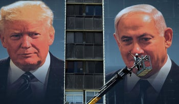 A laborer stands on a crane as he puts up banners depicting Trump and Netanyahu in Jerusalem, June 10, 2020.