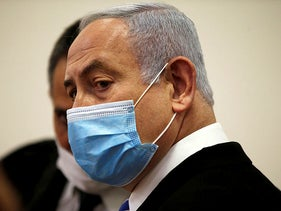 Israeli Prime Minister Benjamin Netanyahu, wearing a face mask, looks on while standing inside the court room as his corruption trial opens at the Jerusalem District Court, May 24, 2020.