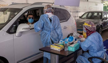 A health worker wearing protective gear prepares to take swab samples at a drive-through COVID-19 screening center at Ain Shams University in Cairo, June 17, 2020.