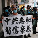 An anti-national security law protester holds a banner reading 'Chinese communist party is shameless, break the promises' during a march at the anniversary of Hong Kong's handover to China from Britain in Hong Kong,  July 1, 2020.