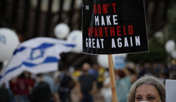 A protester against annexation holds a sign in Tel Aviv on June 23, 2020.