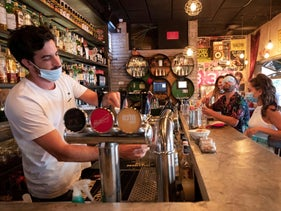 A bartender and customers wear face masks to fight the spread of the coronavirus disease at a bar in Tel Aviv, June 4, 2020.