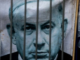 An image of Netanyahu on a placard is seen through a fence during a demonstration against the Israeli Prime Minister, June 2020.