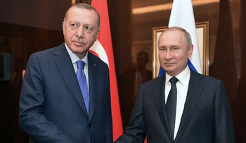 Russian President Vladimir Putin and his Turkish counterpart Tayyip Erdogan shakes hands during their meeting on sideline of the Libya summit in Berlin, Germany January 19, 2020.