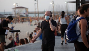 A man wearing a mask and talking on a cellphone by the beach in Tel Aviv, May 2020.