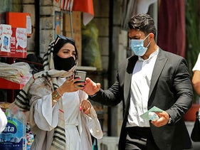 Iranian pedestrians wearing protective masks due to the COVID-19 pandemic, walk along a street in Tehran on July 1, 2020.