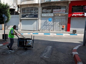 A municipal worker walks in front of closed shops along a street in the West Bank city of Ramallah on July 6, 2020.