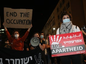 """A demonstration in Tel Aviv against any annexation in the West Bank, June 6, 2020. A protester is holding a sign stating """"Stop Annexation."""""""