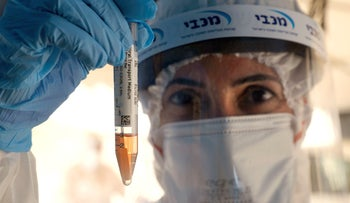 Medical personnel take samples at a drive through COVID-19 testing facility in a Tel Aviv suburb, July 6, 2020.