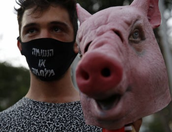 A protester with the inscription 'respiration or war' on his mask at the demonstration against the Israeli government's handling of the economic crisis caused by the coronavirus pandemic holds a pig mask, Tel Aviv, July 11, 2020