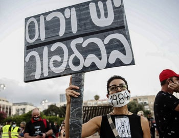 A protester holding up a sign that reads 'There's a virus in Balfour' at a demonstration against poor government financial aid during the coronavirus crisis, Tel Aviv, July 11, 2020