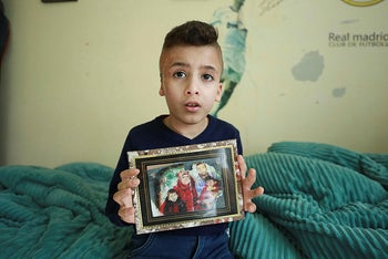 10-year-old Ahmed Dawabsheh shows a family photo partially burnt down at the house in Nablus, West Bank on June 13, 2020.