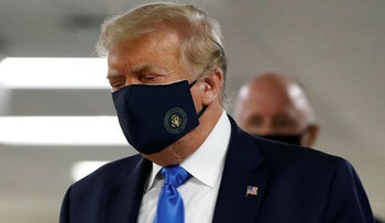 President Donald Trump wears a face mask as he walks down a hallway during a visit to Walter Reed National Military Medical Center in Bethesda, Md., Saturday, July 11, 2020