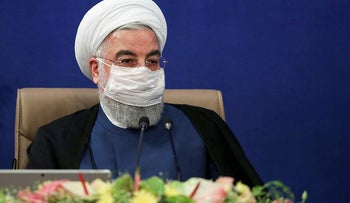 A handout picture provided by the Iranian presidency on July 8, 2020 shows President Hassan Rouhani wearing a face mask, measure against the COVID-19 coronavirus pandemic, while attending a cabinet session in the capital Tehran