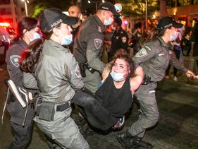 A woman being carried away by police officers during the coronavirus economic protest in Tel Aviv, July 12, 2020.