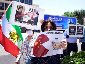 A woman holds a sign as Iranian-Americans protest China's bypassing of US sanctions in doing business with Iran, as well as the handing over of Kish island in the Persian Gulf to China in exchange for military, regional and international support, in front of the Chinese Consulate in Los Angeles, California on July 10, 2020