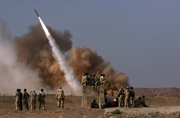 Members of Iran's Revolutionary Guards watch the launch of a missile during military maneuvers in Qom, Iran, June 28, 2011