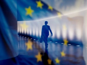 A man walks as he is reflected in an EU flag which is displayed on an information wall in Berlin, Germany, July 2, 2020.