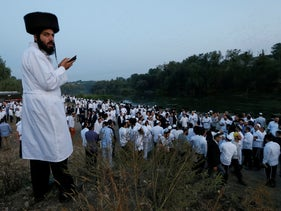 Hasidic Jewish pilgrims pray on a bank of a lake near the tomb of Rabbi Nachman of Breslov during the celebration of Rosh Hashanah in Uman, Ukraine, September 21, 2017.