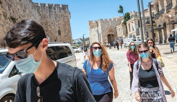 Masked Israelis walking at Jerusalem's Old City in the coronavirus summer of 2020.