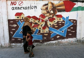 A Palestinian woman walks with her son past a mural in protest of Israel's plan to annex parts of the Israeli-occupied West Bank, in Rafah in the southern Gaza Strip July 14, 2020