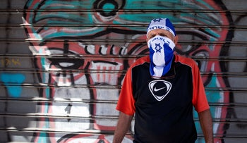 A toy store employee wears an improvised protective face mask in the colors of the Israeli flag while calling for customers outside the store. Tel Aviv, Israel, April 28, 2020
