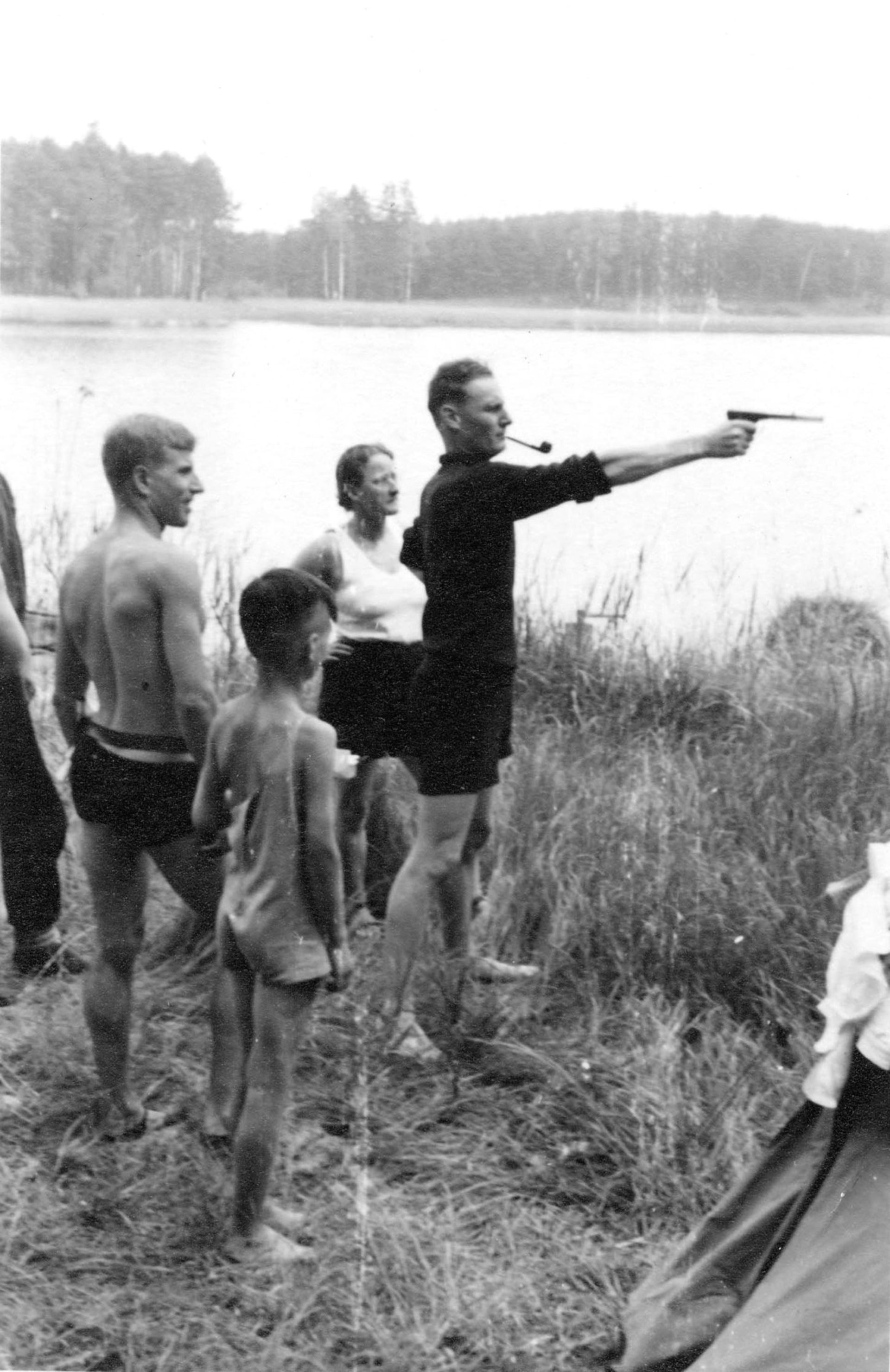 """Harro Schulze-Boysen (with pipe and revolver) taking aim. With him are fellow """"group"""" members Dr. Elfriede Paul and Kurt Schumacher."""