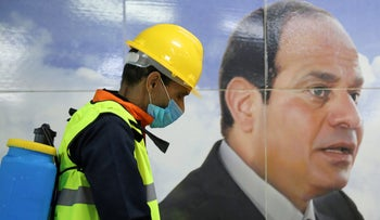 A member of a medical team is seen beside a banner for Egyptian President Abdel Fattah el-Sisi, as he sprays disinfectant amid a COVID-19 outbreak in Cairo, Egypt, on March 22, 2020.