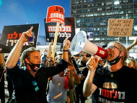 Israelis lift placards and chant slogans during a demonstration in Rabin Square in the central coastal city of Tel Aviv, on July 11, 2020.
