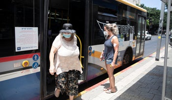 An elderly passenger wearing a protective face mask gets off a bus in Tel Aviv, July 2020.