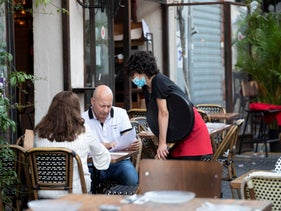 Restaurant goers and a masked waitress at a restaurant in Jaffa, July 9, 2020.