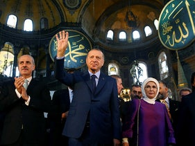 Turkey's President Recep Tayyip Erdogan, centre, accompanied by his wife Emine, right, waves to supporters as he walks in the Byzantine-era Hagia Sophia, Istanbul, March 31, 2018.